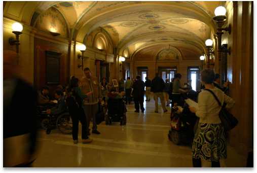 A typical hall of a legislature, with tourists, lobbyists, advocates with disabilities, and legislators moving about.