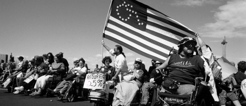 A large crowd of persons using wheelchairs carrying an American-style flag with stars in the form of a wheelchair, charging across a hill.