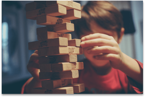 Young child playing Jenga, a board stacking game where the object is to pull wooden parts from the stack without causing a collapse of the tower.