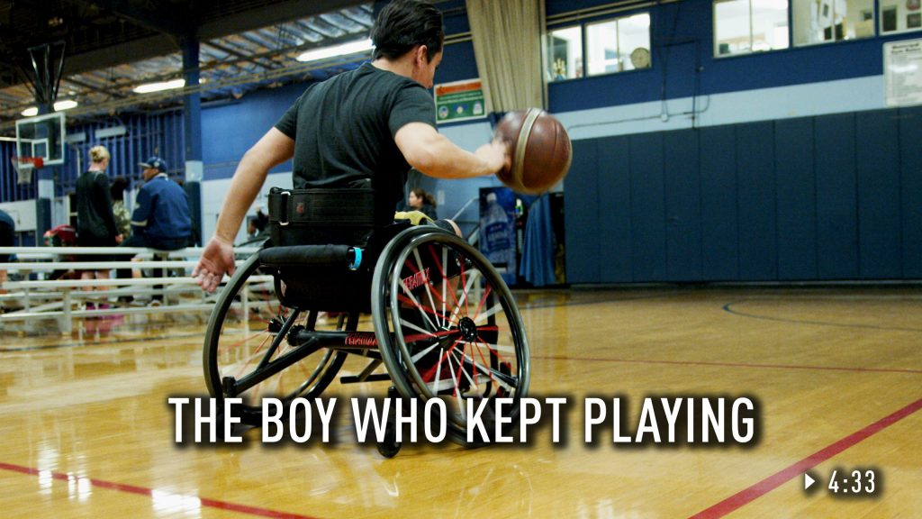 Danny dribbling down the basketball court in his wheelchair.