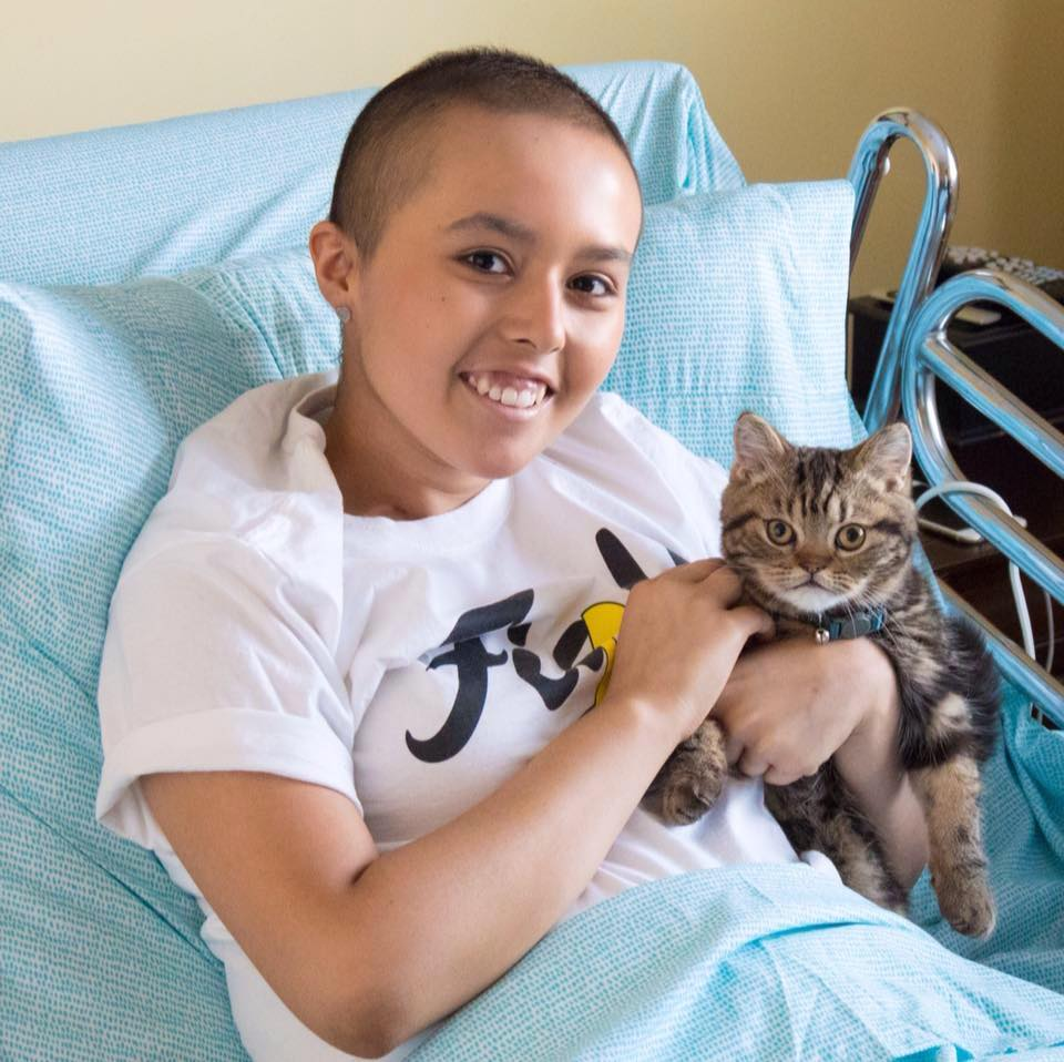 Anissa in a hospital bed with a cat.
