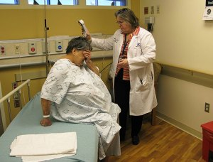 Marcy Smith, a geriatric social worker attends to a patient. ERs usually don't have a full-time social worker, and all doctors and nurses in this ER are trained in geriatrics. Joe Shapiro/NPR