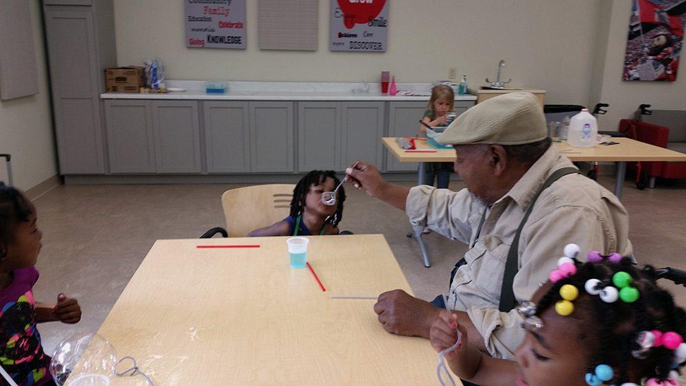 Elder Playing with Child - Champion Center