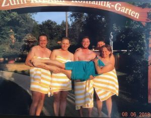 Group of 4 friends in towels, holding a 5th person in front of them.