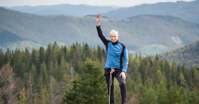 Woman Raising Hand and Smiling with Climbing Gear - ChangingAging
