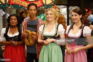 trois femmes de couleurs distinctes habillées d'habit traditionnels allemands jouent les poticles avec au milieu un grand homme de couleur à l'air nigaud qui tient un bretzel