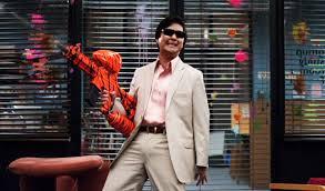un asiatique en costard et lunettes noires tient un fusil de paintball dans une pose cool mais un peu tarée