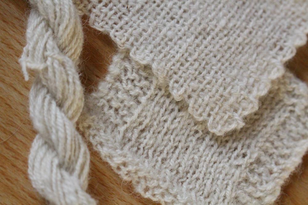 Handgesponnenes Garn vom Walliser Schwarznasen Schaf mit einer verstrickten und einer gewebten Probe