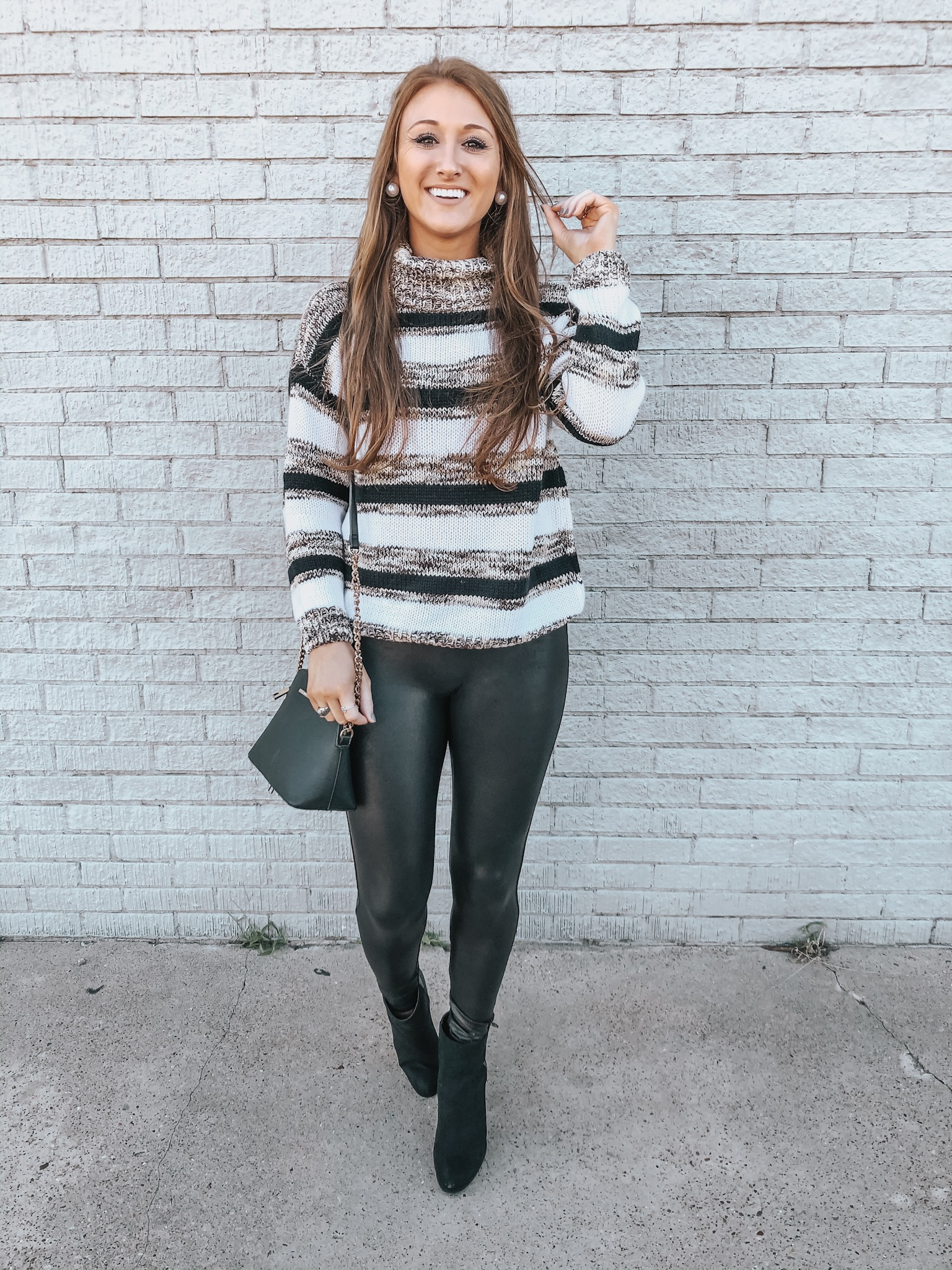 Carrington of Chaos and Coffee in a colorblock sweater, Spanx faux leather leggings and black booties