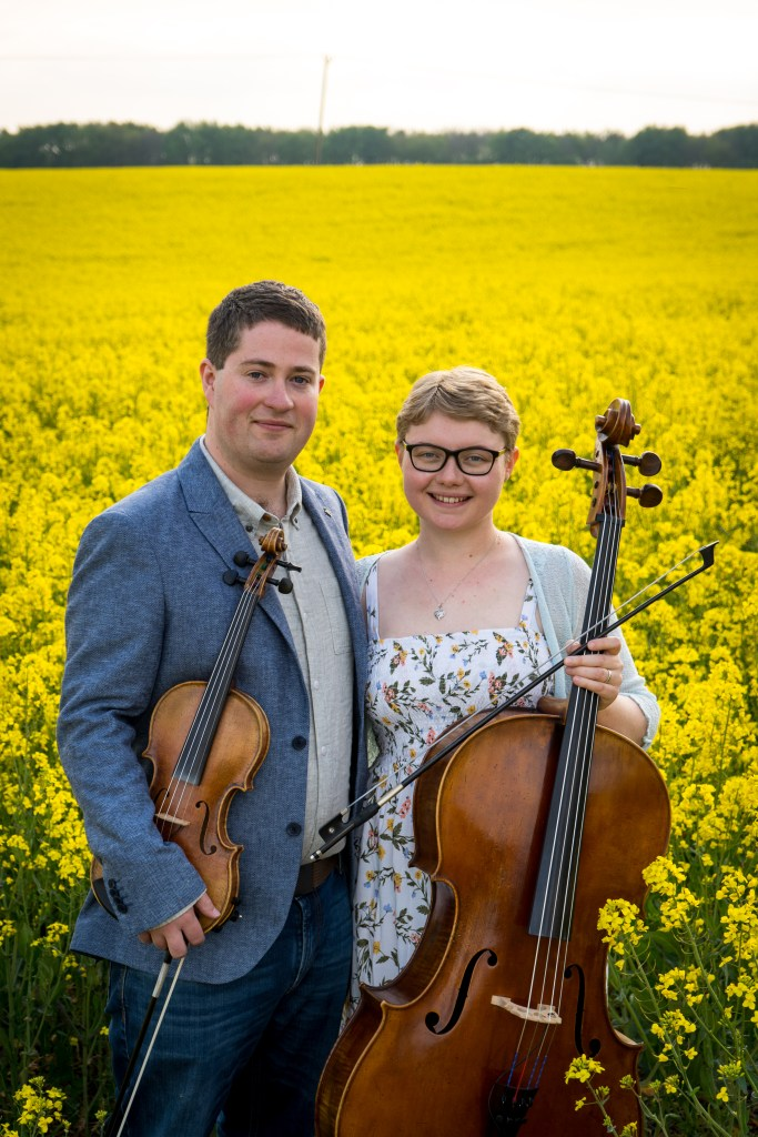 The Chapel Hill Duo, violinist Jaya Hanley and Cellist Sarah James. Headshot in field of yellow flowers.