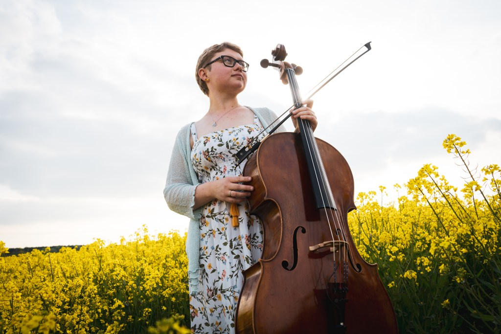 Sarah James of the Chapel Hill Duo poses with her cello in a field.