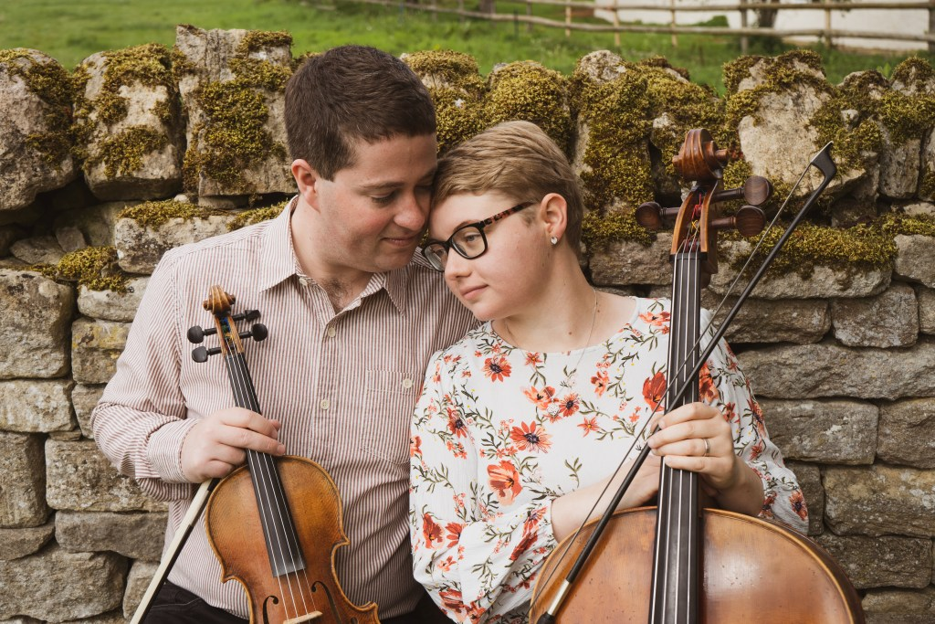 The Chapel Hill Duo, Jaya Hanley Violinist and Sarah James Cellist share a romantic moment sitting on a bench in front of a drystone wall covered in moss.