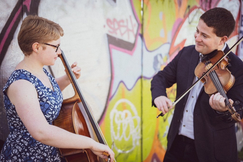 Jaya Hanley and Sarah James perform on the Violin and Cello in front of graffiti.