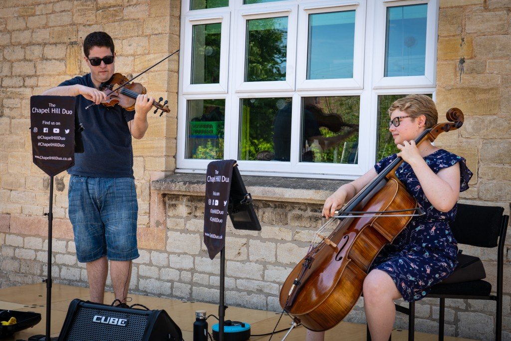 Jaya Hanley and Sarah James perform their Violin and Cello cover versions of popular songs at a summer fete.
