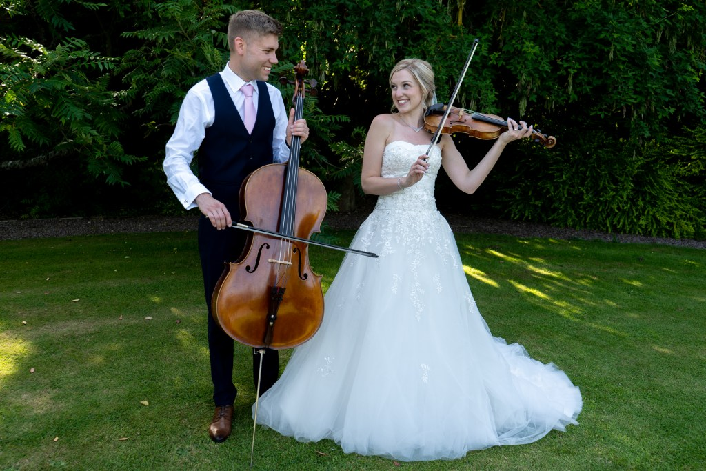 A bride and groom play a violin and a cello at a wedding drinks reception.