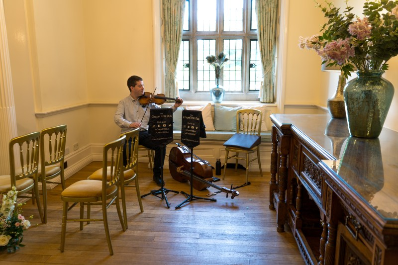 Jaya Hanley tuning his violin before the wedding ceremony at Lanwades hall.