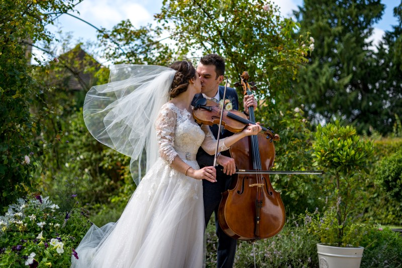 bride with violin and Groom with cello share a kiss with wedding dress veil blowing behind them.