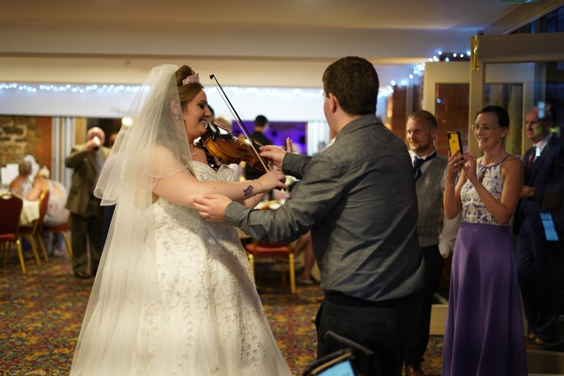 Violinist jaya hanley giving a violin lesson to a bride on her wedding day.
