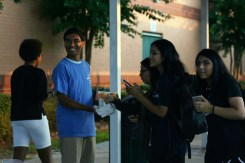 Student Council Representative Hrishi Mungala (11) hands out donuts under the bus canopy.
