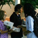 Student Council Representatives Susie Browder (10) and Kamal Korrapati (10) hand out donuts under the bus canopy.