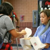 Student Council Representative Mimi Do (11) hands out a donut by the Senior Parking Lot Entrance.