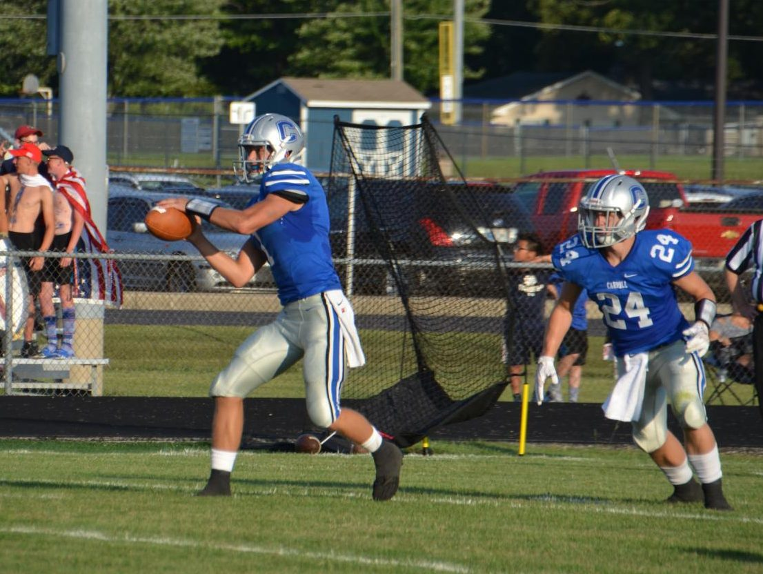 Seen here against Bishop Luers in the season opener, Jack Miguel takes the snap from center before a fake to running back Cam Shank. Photo by Hannah Harper