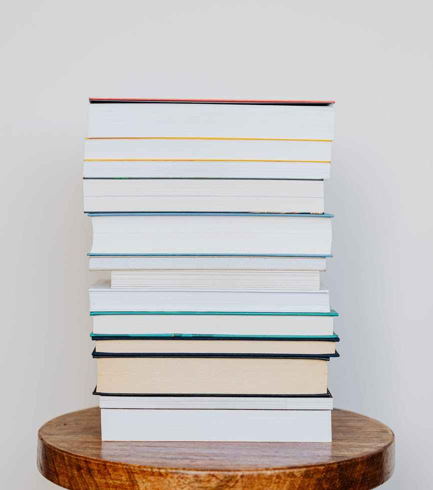 big pile of books on wooden stool