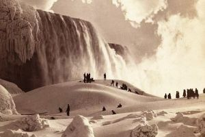 People on snow-covered ice at the base of the frozen American Falls, Niagara Falls, New York. By George Barker.