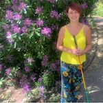 Picture of Nina Chesworth by a colourful bush in summer