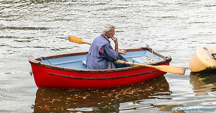 Man in boat in Aberaeron Harbour, photographed by Charles Hawes