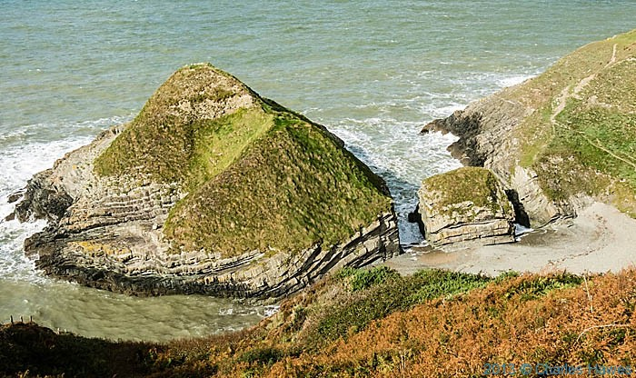 conical island opposite Castell Bach in Ceredigion, photographed from The Wales Coast Path by Charles Hawes
