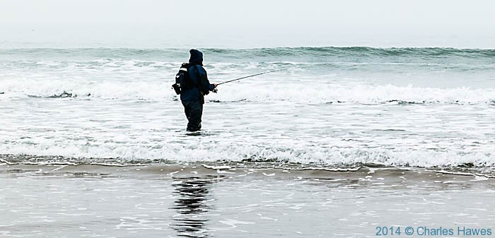 Fishing in the surf at Harlech, photographed from The Wales Coast Path by Charles Hawes