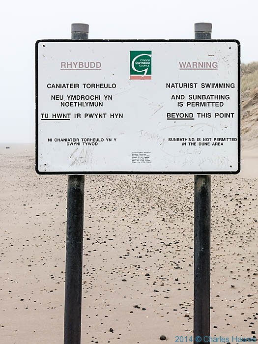 Naturist swimming sign on beach near Llanenddwyn, photographed from The Wales Coast Path by Charles Hawes