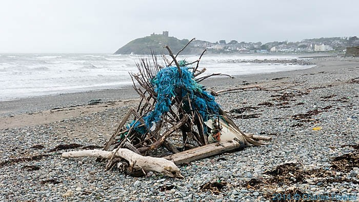 Hut made from flotsam and jetsum on the beach at Criccieth, photographed by Charles Hawes