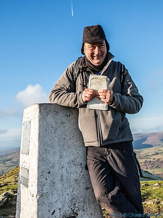 Charles Hawes at the trig point on Sugar Loaf, near Abergavenny, photographed by Paul Steer (under instruction)