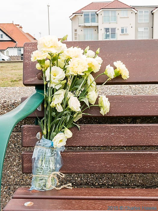 flowers tied to seat on sea front near Llandudno, photographed from The Wales Coast Path by Charles Hawes