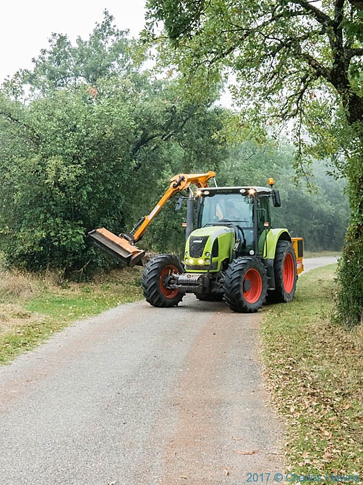 Tractor trimming hedgerow in Genibrousse wood, France, photographed by Charles Hawesin