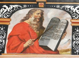 Moses pointing to a tanlet of stone