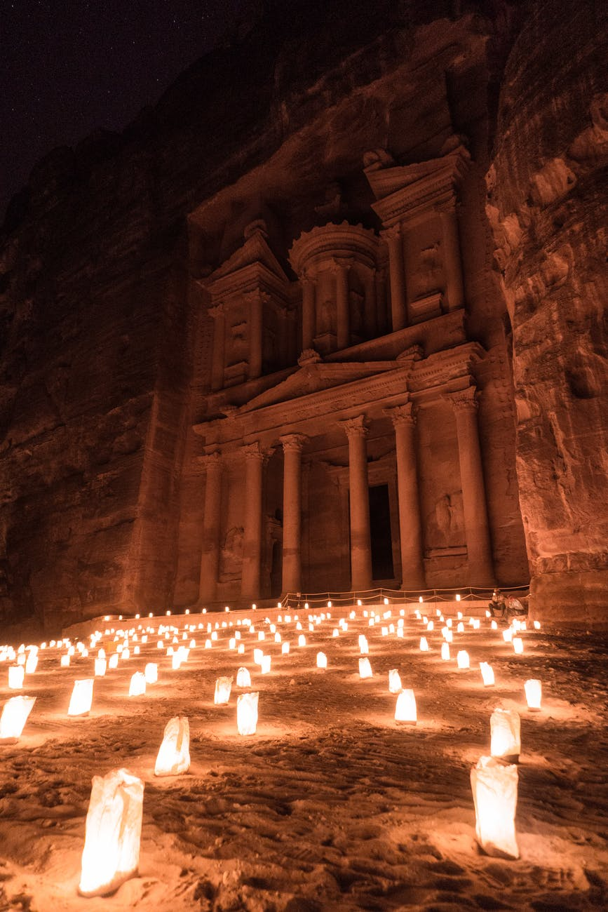 lighted candles in front of brown concrete building