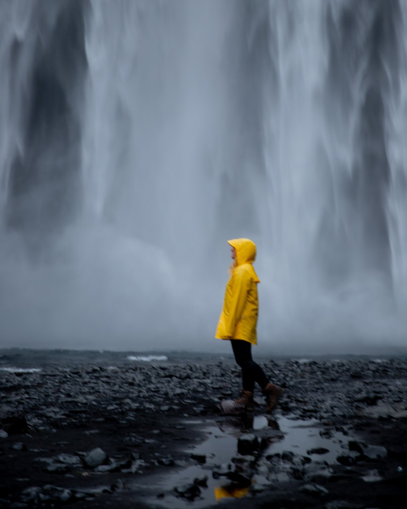 Girl in yellow jacket in front of Skogafoss