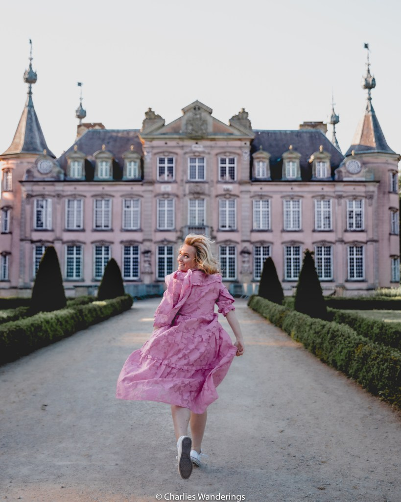 Girl in pink dress in front of pink castle