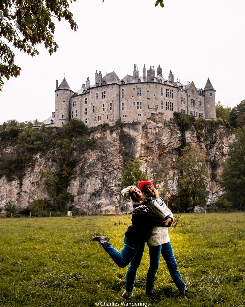 two girlfriends hugging in front of castle on a cliff