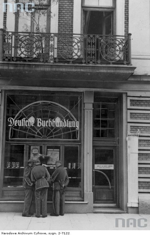 Trzej żołnierze przed niemiecką księgarnią. 1940. Źródło: https://audiovis.nac.gov.pl/obraz/10834/2354ed7d08876ba174fad10ab2574332/