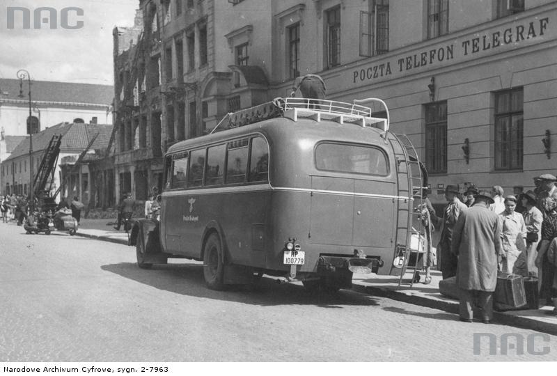 Lublin. Autobus dalekobieżny na przystanku przed urzędem pocztowym. Widoczni pasażerowie z bagażami. 1939-1945. Źródło: https://audiovis.nac.gov.pl/obraz/18249/2354ed7d08876ba174fad10ab2574332/