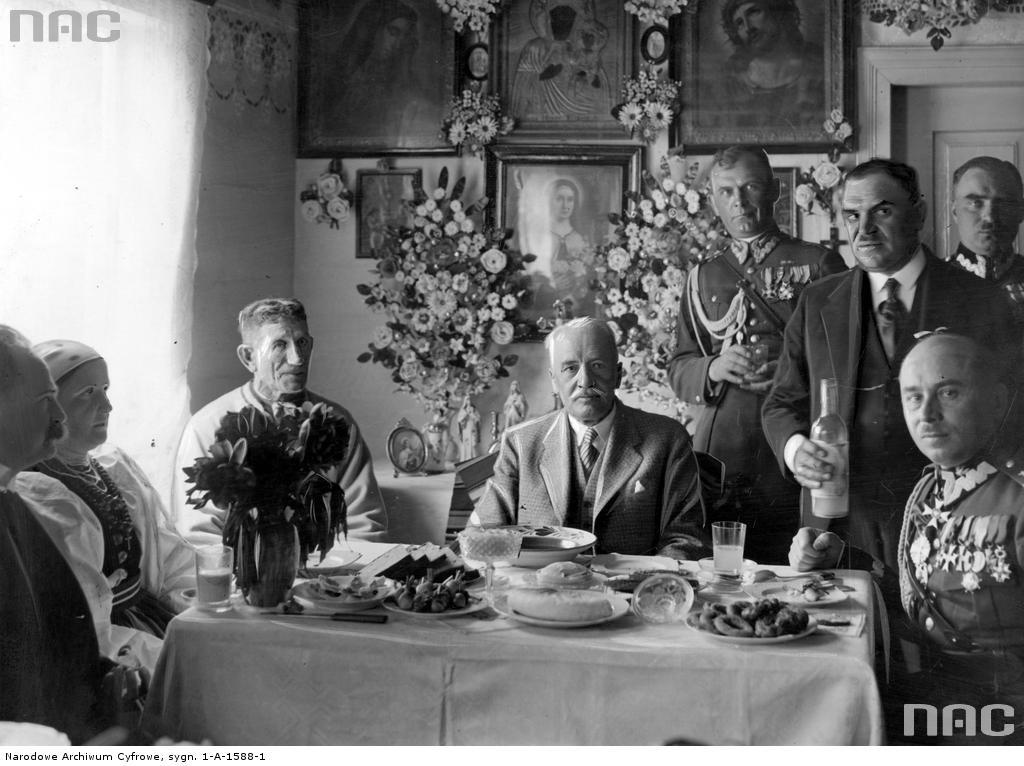 Prezydent Mościcki na obiadku u rodziny chłopskiej. Źródło: https://audiovis.nac.gov.pl/obraz/53087/h:485/