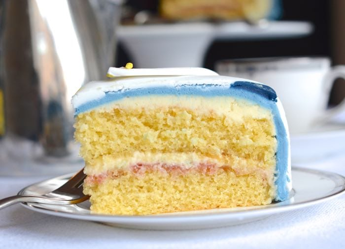 A slice of vanilla birthday cake on a plate filled with jam and vanilla buttercream and covered in blue fondant icing.