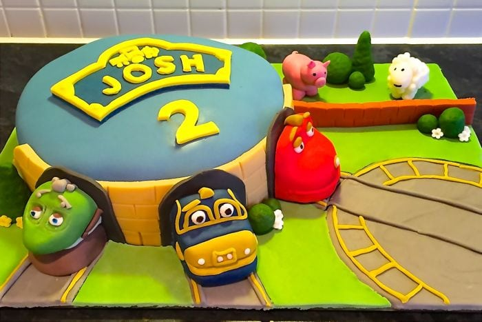 A Chuggington birthday cake. The cake is a blue engine shed with Koko, Wilson and Brewster poking out. There's a train turntable and a farm with a pig and sheep.