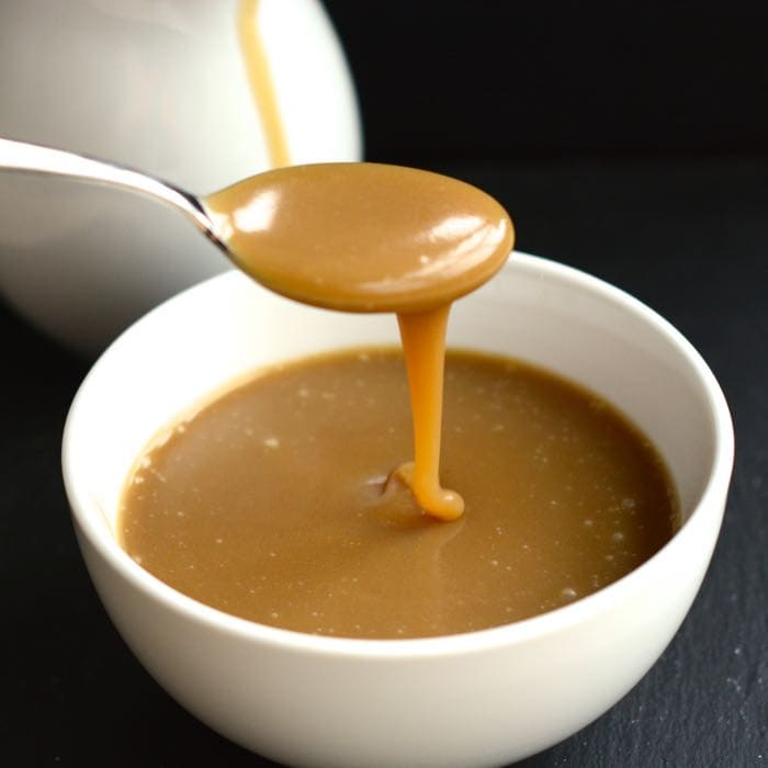 A spoonful of caramel sauce drizzling down into a bowl of sauce.