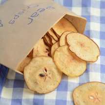 Pear crisps falling out of a homemade crisp packet on a blue and white checked cloth.