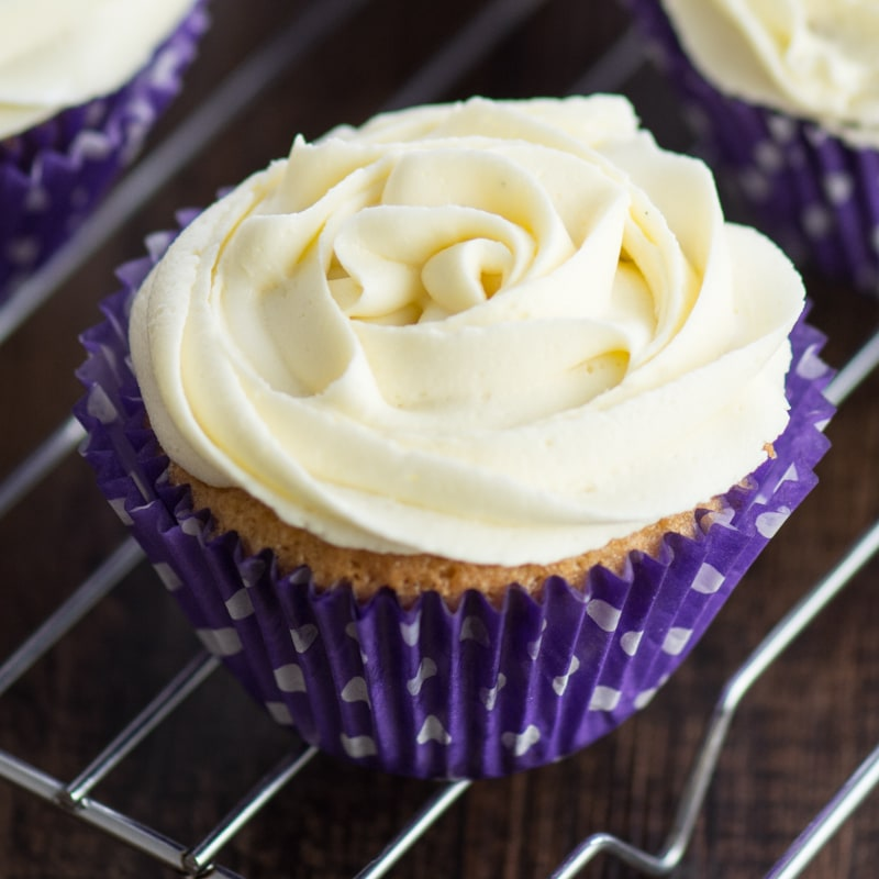A close up of a vanilla cupcake topped with a vanilla buttercream rose in a purple cupcake case.